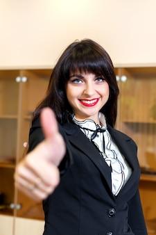 Donna sorridente attraente in ufficio che esamina il pollice della macchina fotografica in su