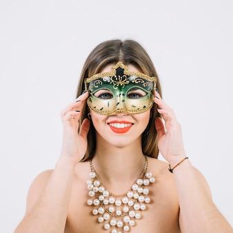 Donna sorridente attraente nella maschera di carnevale di travestimento su fondo bianco