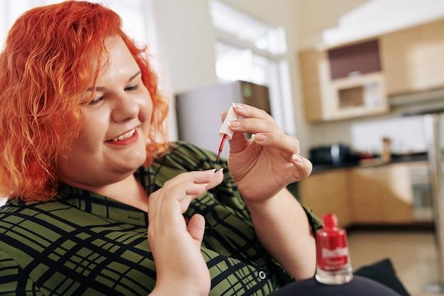 Donna sorridente che applica smalto per unghie
