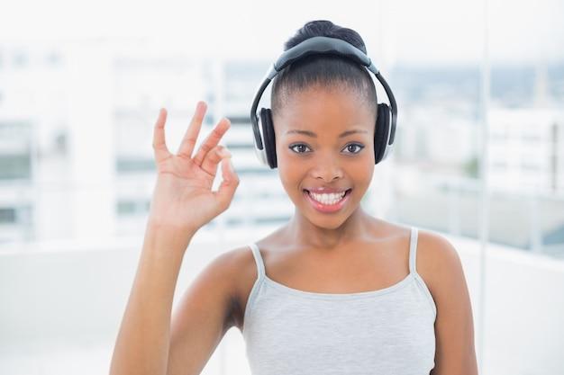 Donna sorridente che ascolta la musica con le cuffie e segno giusto shwoing