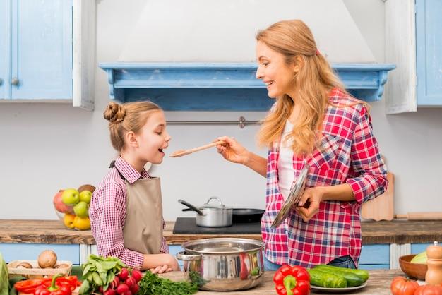 Donna sorridente che assaggia un alimento a sua figlia con un cucchiaio di legno nella cucina