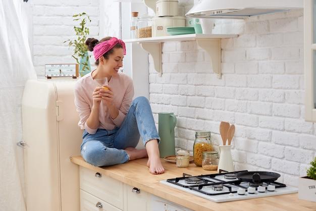 Donna sorridente che beve il succo di arancia nella cucina