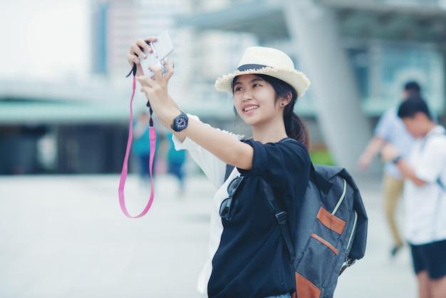 Donna sorridente che cammina all'aperto, giovane signora ammirando la vista della città con passaggio pedonale e edifici in background.