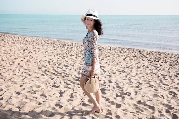 Donna sorridente che cammina sulla spiaggia