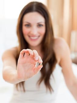 Donna sorridente che cattura una pillola che si siede sul letto