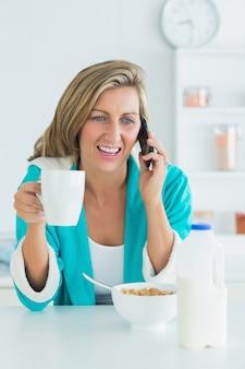Donna sorridente che chiama durante la sua colazione