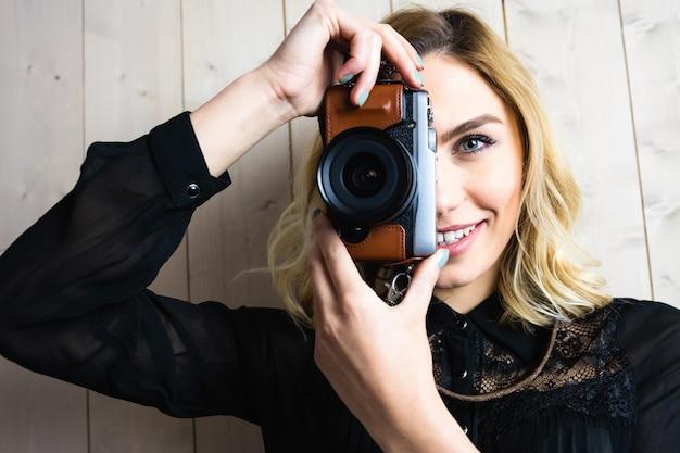 Donna sorridente che clicca foto dalla macchina fotografica