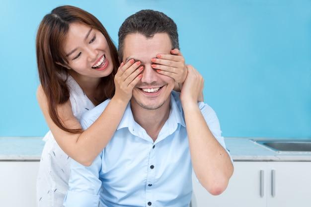 Donna sorridente che copre gli occhi degli uomini in cucina