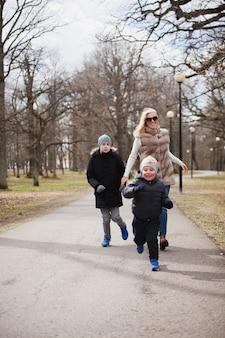 Donna sorridente che corre dietro suo figlio