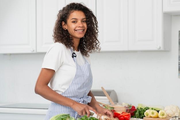 Donna sorridente che cucina e che esamina fotografo