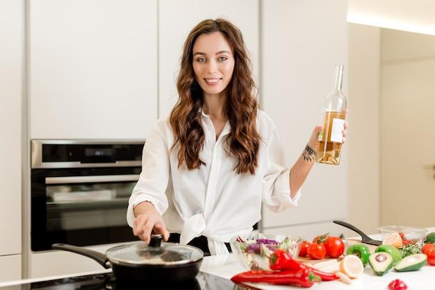 Donna sorridente che cucina la bistecca di pesce fresca con vino bianco e le verdure sulla cucina
