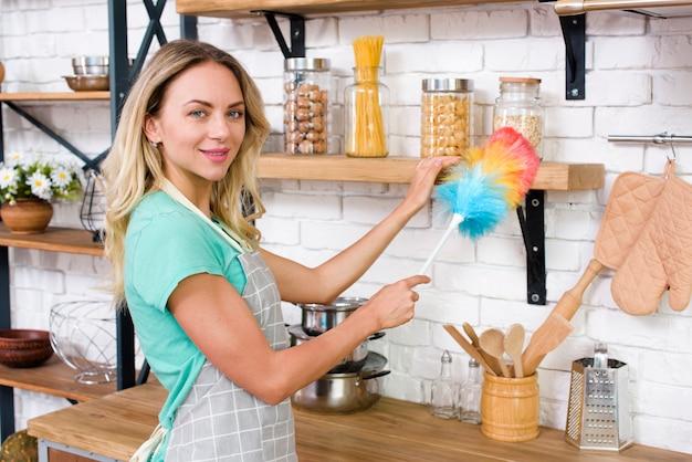 Donna sorridente che esamina macchina fotografica mentre spolverando nella cucina