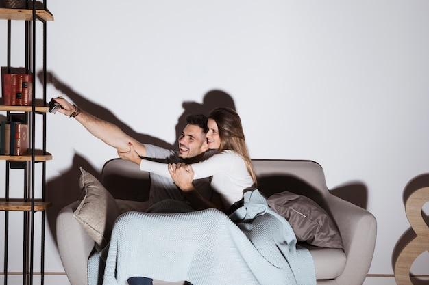 Donna sorridente che ferma uomo per mettere telecomando della tv sullo scaffale sul sofà
