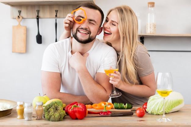 Donna sorridente che gioca con il peperone dolce