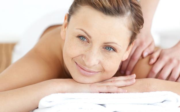 Donna sorridente che gode di un massaggio alla schiena