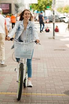 Donna sorridente che guida la sua bici
