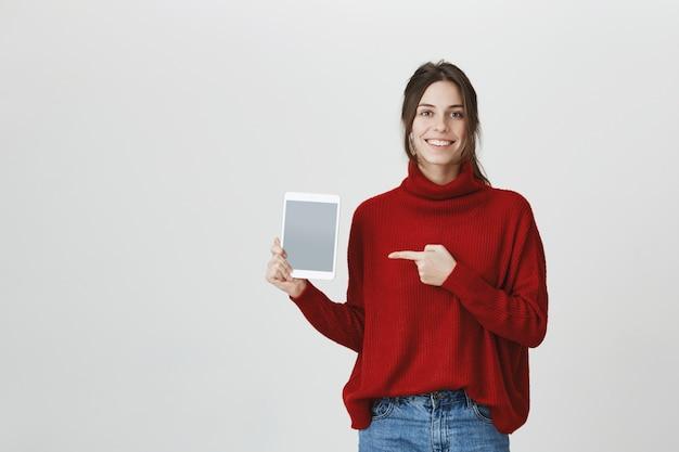 Donna sorridente che indica allo schermo digitale della compressa