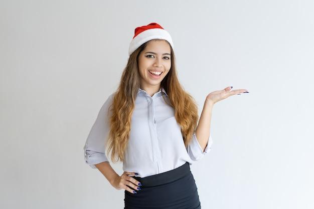 Donna sorridente che indossa il cappello di babbo natale e che presenta il prodotto