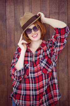 Donna sorridente che indossa un trilby e occhiali da sole