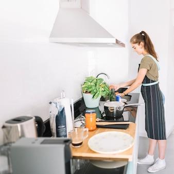 Donna sorridente che lava i pomodori rossi nel lavandino