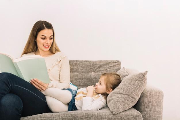 Donna sorridente che legge fiaba alla figlia