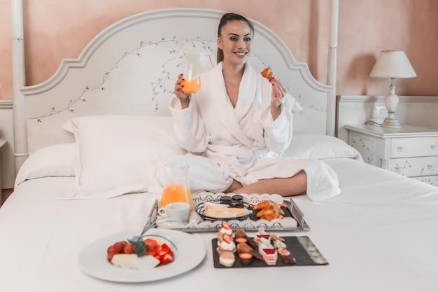 Donna sorridente che mangia prima colazione sul letto