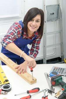 Donna sorridente che monta le plance di legno facendo uso del cacciavite