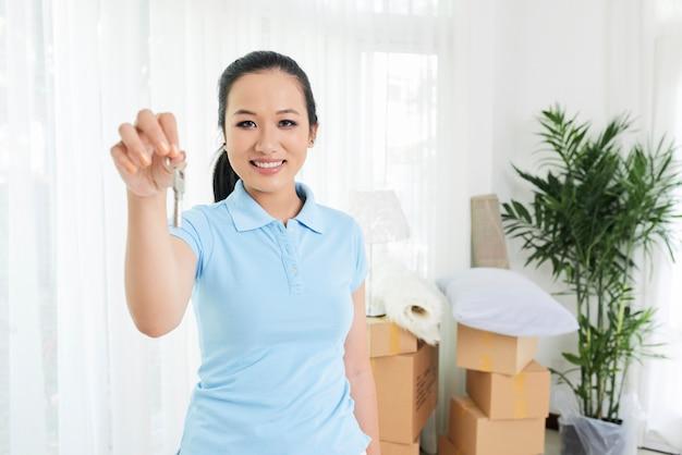 Donna sorridente che mostra chiave di nuovo appartamento