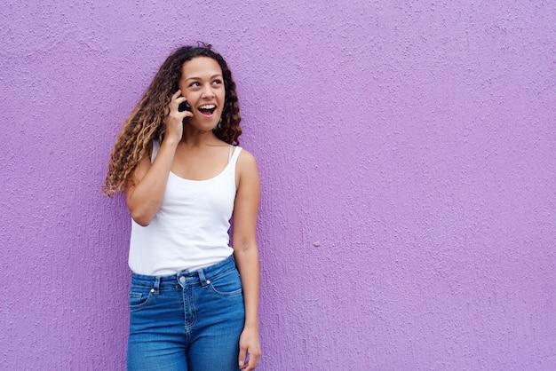 Donna sorridente che parla sul telefono cellulare e che osserva via
