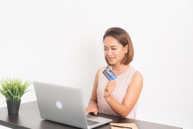 Donna sorridente che passa in rassegna sul suoi computer portatile e carta di credito.