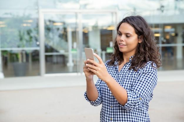 Donna sorridente che per mezzo dello smartphone sulla via