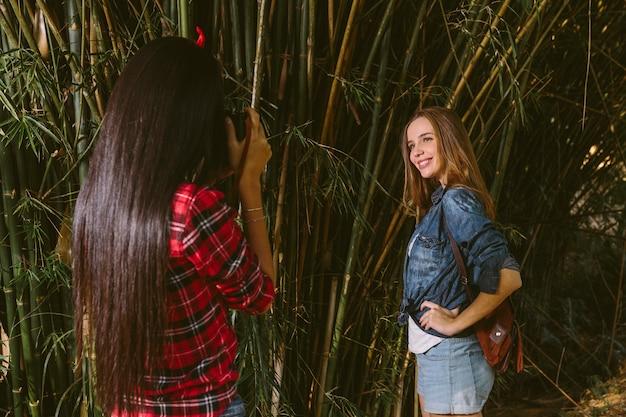 Donna sorridente che posa mentre la sua amica che prende fotografia con la macchina fotografica
