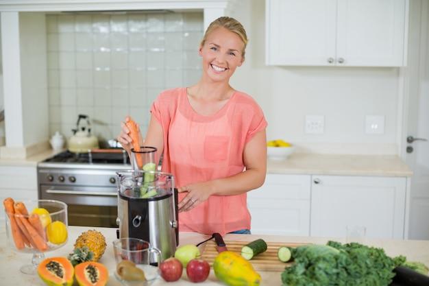 Donna sorridente che prepara il succo di frutta fresca in cucina