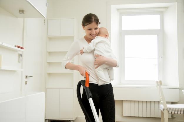 Donna sorridente che pulisce il tappeto che tiene un bambino