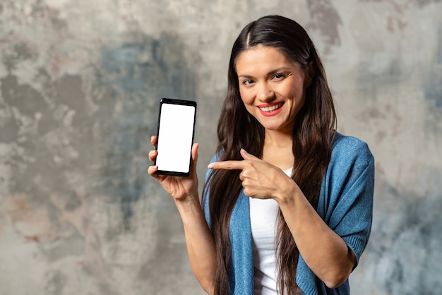 Donna sorridente che punta allo schermo del telefono cellulare.