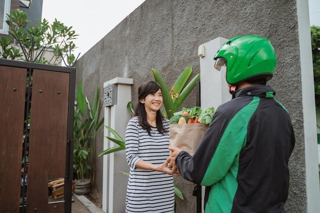 Donna sorridente che riceve la consegna della drogheria a casa