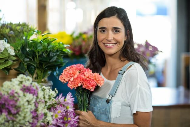 Donna sorridente che seleziona i fiori al negozio di fiorista