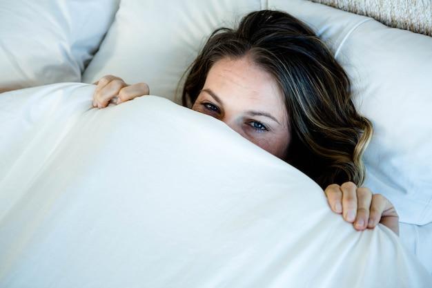 Donna sorridente che si nasconde dietro la sua coperta