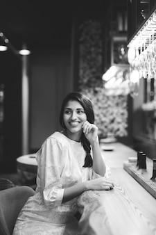 Donna sorridente che si siede al bancone del bar