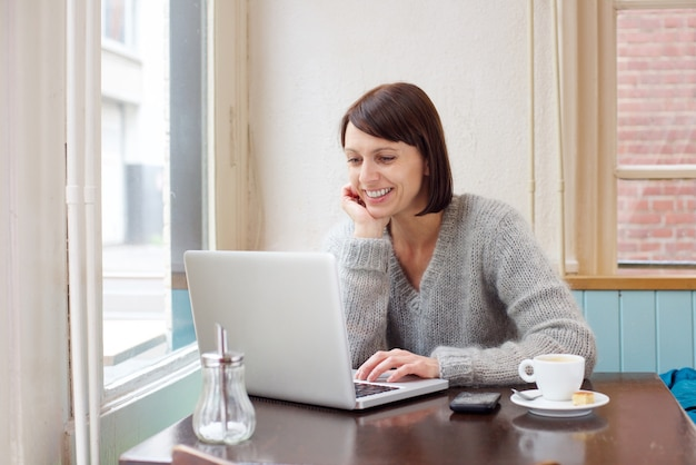 Donna sorridente che si siede al caffè con il portatile