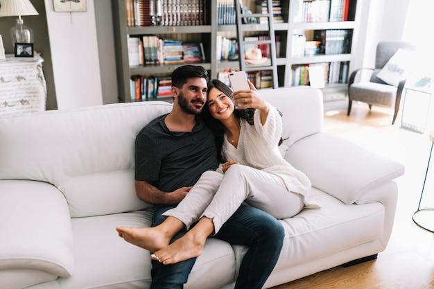Donna sorridente che si siede con il suo ragazzo che prende selfie sul cellulare a casa