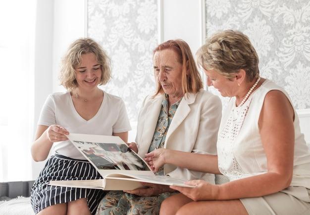 Donna sorridente che si siede con sua madre e nonna che guardano album di foto a casa