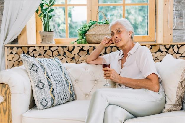 Donna sorridente che si siede sul sofà con la gamba attraversata che tiene vetro di alcool