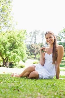 Donna sorridente che si siede sull'erba in un parco