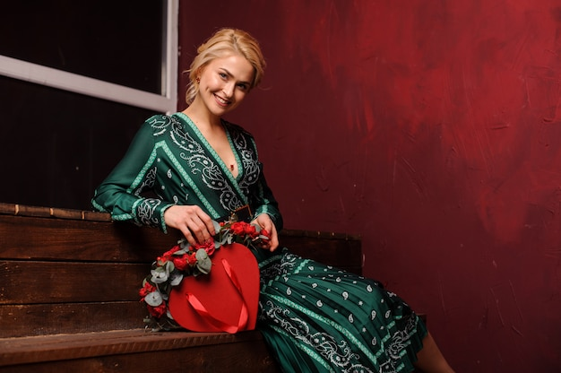 Donna sorridente che si siede sulle scale con una scatola rossa di rose