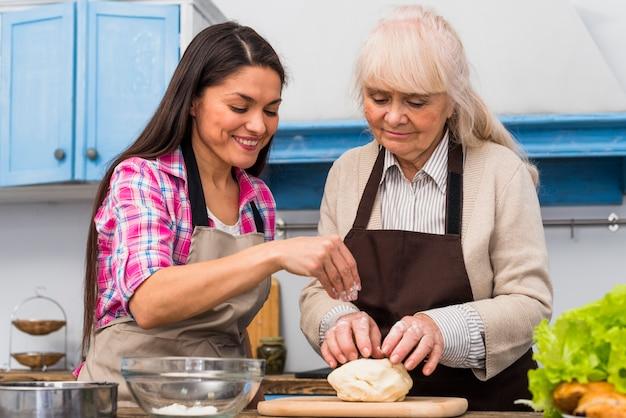 Donna sorridente che spolvera la farina sopra la pasta impastata da sua madre