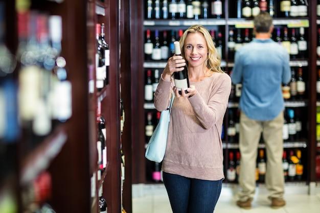 Donna sorridente che tiene bottiglia di vino
