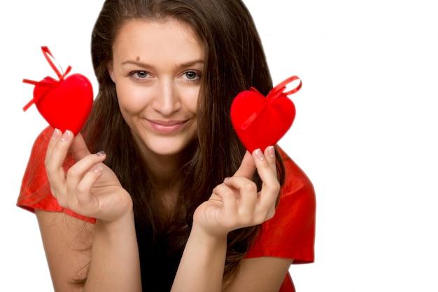 Donna sorridente che tiene due cuori rossi