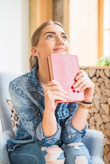 Donna sorridente che tiene il libro con copertina rigida