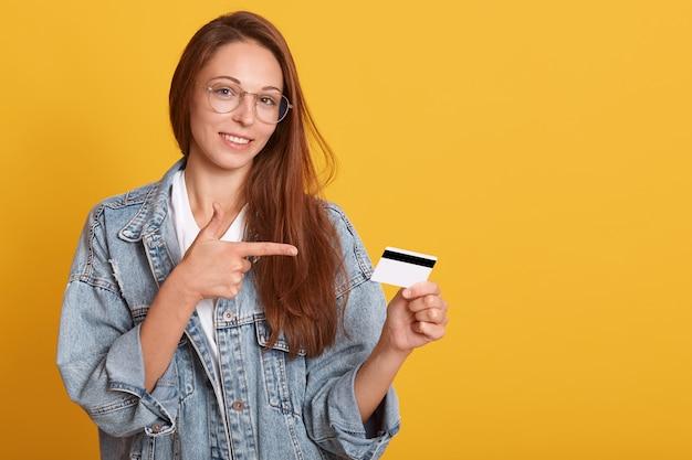 Donna sorridente che tiene la carta di credito dell'oro e che indica su di esso con il suo dito indice, lo spazio della copia per il testo pubblicitario o promotin, la femmina che indossa il rivestimento ed i vetri alla moda del denim, isolati sulla parete gialla.